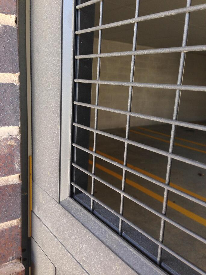 wire-mesh-secured-in-aluminum-panel-sectional-overhead-garage-door-commercial-parking.jpg